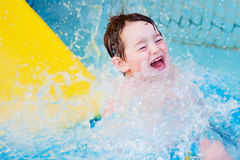 Boy splashes down from water slide Royalty Free Stock Photos