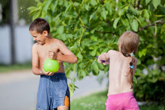 Boy splashes the girl, a balloon filled with water on a summer d Royalty Free Stock Photo
