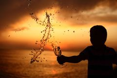 Boy splashes out drink on sea sunset Royalty Free Stock Photos