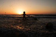 The boy splashes into the sea. With water Royalty Free Stock Photography