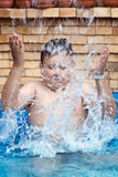 Boy splashes water in swimming pool Royalty Free Stock Images