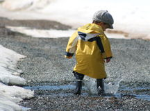 Boy splashing. Young boy with a yellow raincoat splashing in a puddle Royalty Free Stock Photography