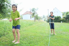 Boy splashing another kid with garden hose. Barefoot little boy - smiling kid in wet clothes standing and splashing and soaking wet another boy with garden hose stock image