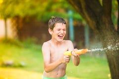 Boy splashing  children with water gun, sunny summer garden Stock Image