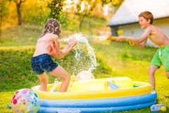 Boy splashing girl with water gun, garden swimming pool Stock Images