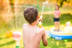 Boy splashing girl with water gun, garden swimming pool Stock Photo