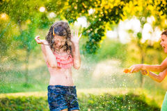 Boy splashing girl with water gun, sunny summer garden Stock Photography