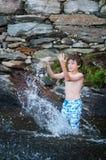 Boy splashing in a lake. Young boy playing in a lake in Haliburton County Ontario stock photo