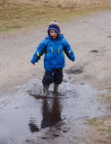 Boy splashing in a muddy puddle Royalty Free Stock Photography