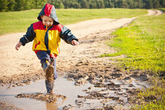 Boy splashing in puddle Royalty Free Stock Photography