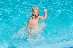 Boy splashing in the water. Happy boy splashing in the water stock images