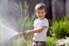 Boy, splashing water with a hose. Having fun stock photos