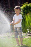 Boy, splashing water with a hose Royalty Free Stock Image
