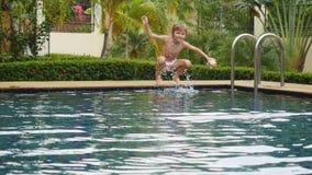 Boy splashing water into a swimming pool Royalty Free Stock Photos