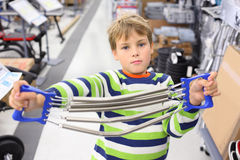 Boy in sports shop holds metal shoulder expander. With springs and looks at camera Royalty Free Stock Images