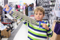 Boy in sports shop tries metal shoulder expander Royalty Free Stock Image