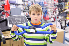 Boy in sports shop tries shoulder expander. Boy in sports shop tries blue shoulder expander and looks at camera Stock Images