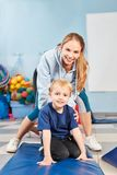 Boy and sports teacher at the kids gymnastics stock photography