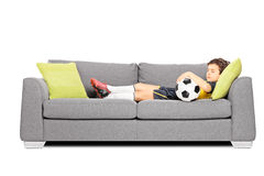 Boy in sportswear with a soccer ball sleeping on a modern sofa. Isolated on white background Stock Photo