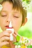Boy spraying his nose. Little boy spraying his nose outdoors Stock Photos