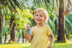 Boy spraying insect repellents on skin. In the park stock photo