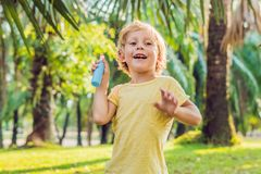 Boy spraying insect repellents on skin. In the park stock photography