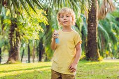 Boy spraying insect repellents on skin. In the park stock images
