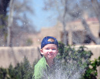 Boy spraying water. A view of a little boy spraying water outdoors on a bright, sunny day Stock Images