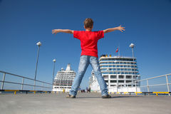 Boy spread hands against background two ships Royalty Free Stock Image