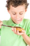 Boy spreading peanuts butter on bread Stock Image