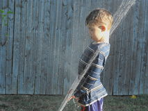 Boy in the Sprinkler. Little boy playing in the sprinkler stock photos