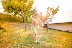 Boy at the sprinkler having fun, summer garden Royalty Free Stock Photos