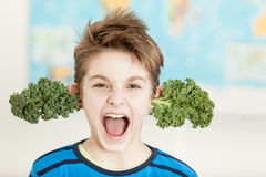 Boy sprouting fresh kale leaves from his ears Royalty Free Stock Image