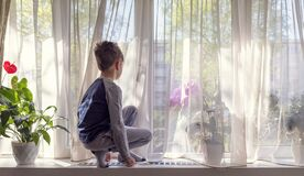 Free Boy Squatting And Looking Through Window Stock Photo - 179047970
