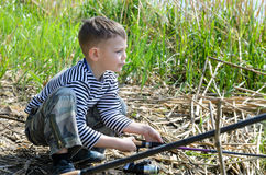 Boy Squatting at the Riverside Holding Fishing Rod Royalty Free Stock Photo