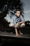 Boy squatting on a table Stock Photography