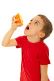 Boy squeeze orange to his mouth Royalty Free Stock Photos