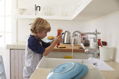 Boy squeezing washing up liquid into sink to wash dishes Stock Photo
