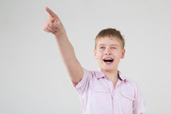 The boy squinted and points a finger somewhere. The boy in a pink shirt squinted and points a finger somewhere Stock Photo