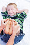 Boy squinting funny tickling feet Stock Photography