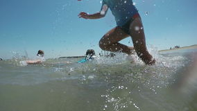 Boy squirting and jumping into the coastal waves stock video footage