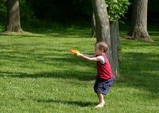 Boy Squirting Squirt Guns. Boy having fun playing with squirt guns outside Stock Photos