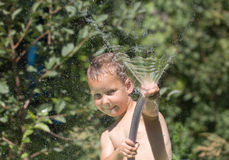 Boy squirting water from a hose Royalty Free Stock Photography