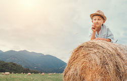 Boy in sraw hat lying on hay roll Stock Photos