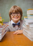Boy with stack of books in classroom Royalty Free Stock Images