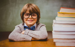 Boy with stack of books in classroom Royalty Free Stock Photo