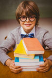 Boy with stack of books in classroom Stock Photo