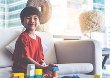 Boy stacking Toy blocks on a living room for educational toy royalty free stock photo