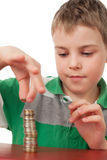 Boy stacking up coins isolated on white Stock Photography