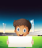 A boy at the stadium holding an empty cardboard Stock Image